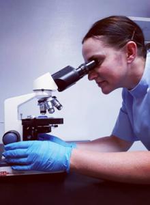Vet looking through microscope